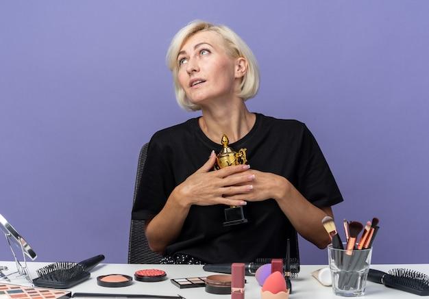Een blij uitziende jonge, mooie meid zit aan tafel met make-uptools met een winnaarbeker geïsoleerd op een blauwe muur