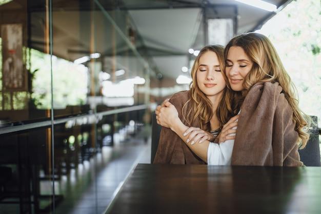 Een blije familie! de jonge mooie dochter van een blonde en haar moeder van middelbare leeftijd omhelzen