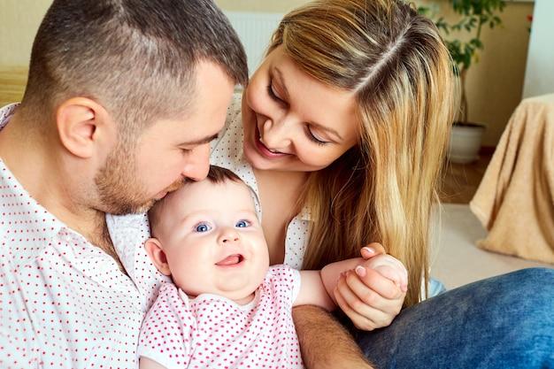 Een blije familie. mamma en papa met baby in de kamer