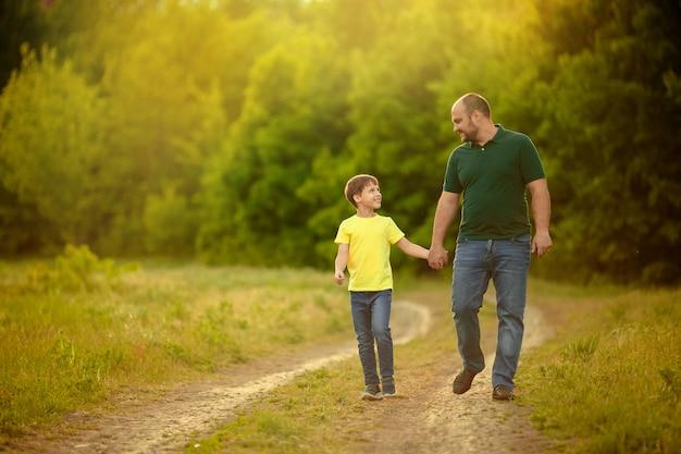 Een blije familie. vader en zoon lopen langs de weg en houden elkaars hand vast voor een boswandeling.