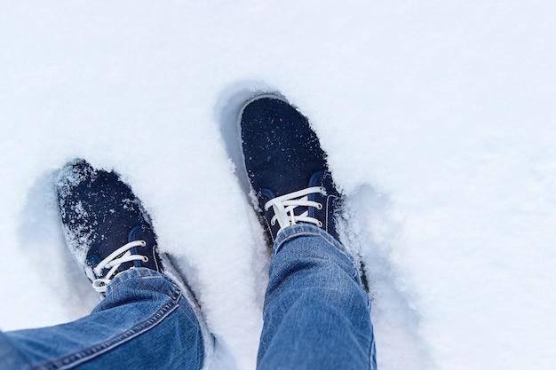 Een blik van bovenaf op blauwe sneakers in een sneeuw.