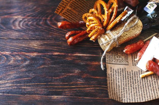 Een blikje bier met een snack op een houten donkere achtergrond. cadeau boeket aan een man. vakantiecadeau voor mannen