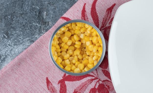 Een blikje vol popcornzaadjes met een leeg bord op tafelkleed.