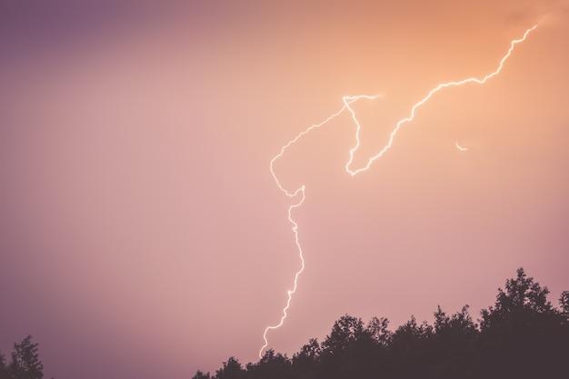 Een bliksemschicht in de lucht boven het silhouet van het bos.
