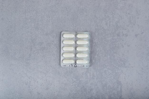 Een blister met witte pillen op een grijs oppervlak