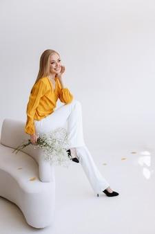 Een blogger in stijlvolle kleding in een licht interieur lacht. vrije ruimte voor tekst