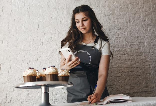 Een blogger maakt foto's van taarten en cupcakes voor haar abonnees op haar telefoon