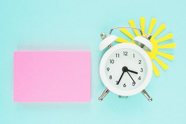 Een blok roze stickers, een witte wekker en een gele papieren zon gluren van achteren op een blauwe papieren achtergrond.