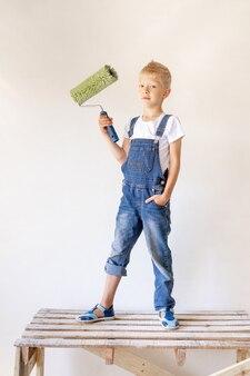 Een blond kind staat op een bouwladder in een appartement met witte muren en een roller in zijn handen, een plek voor tekst, het concept van reparatie