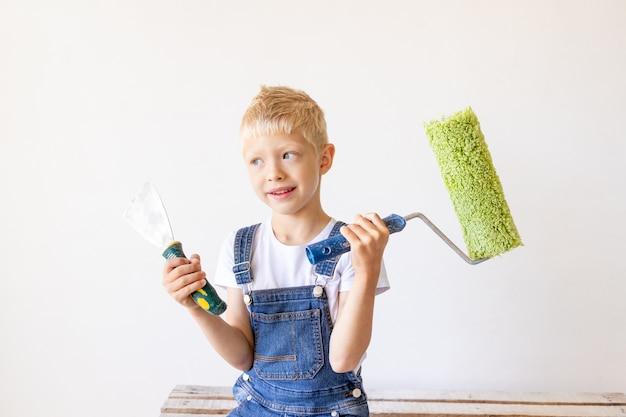 Een blond kind staat op een bouwladder in een appartement met witte muren en een roller in zijn handen en kijkt in de verte, een plek voor tekst, het concept van reparatie