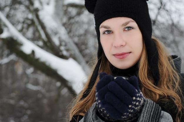 Een blond langharige meisje in een grappige hoed met panda oren drinkt koffie op een winterse dag buiten