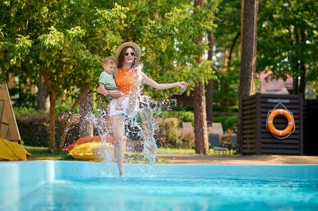 Een blond meisje dat bij het zwembad zit
