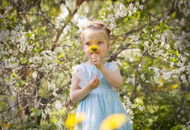 Een blond meisje dat een gele bloem ruikt