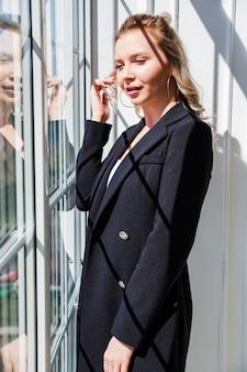 Een blond meisje in een zwart pak staat bij het raam en geniet van het zonlicht.