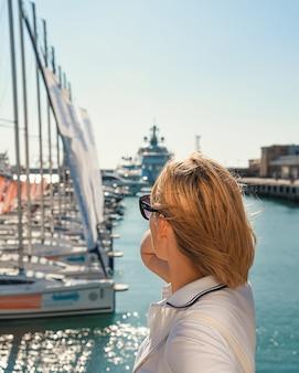 Een blond meisje kijkt naar de zee en de jachten.