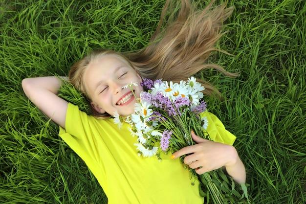 Een blond meisje met een boeket madeliefjes in haar handen op de achtergrond van de natuur.