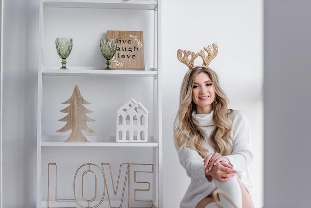 Een blond meisje met gouden kerst herten hoorns in een grijze gebreide trui, lange legging zit op de vensterbank bij het panoramische raam. er is een wit rek met huisbeeldjes. kopieer de ruimte wazig