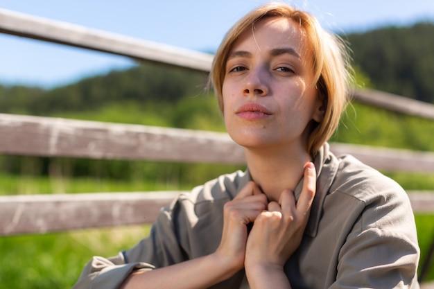 Een blond meisje met kort haar en een grijs shirt zit in een veld op een zonnige dag