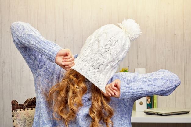 Een blond meisje met lang haar in een gebreide trui trok een witte gebreide muts over haar gezicht