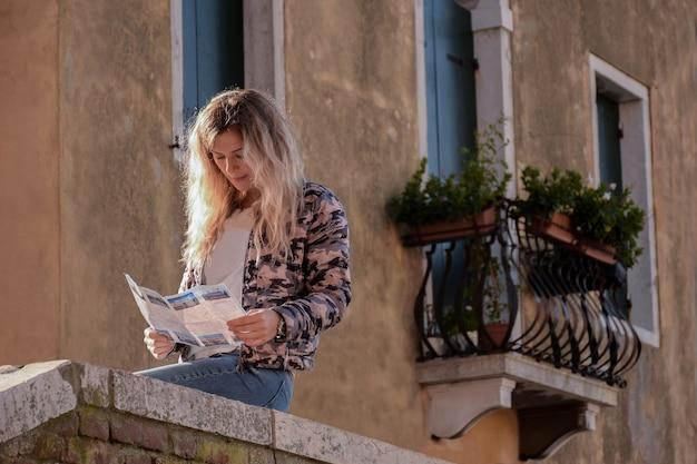 Een blond meisje zit op een stenen borstwering in de buurt van een oud gebouw op de achtergrond van een vintage balkon in bloemen en leest een tijdschrift