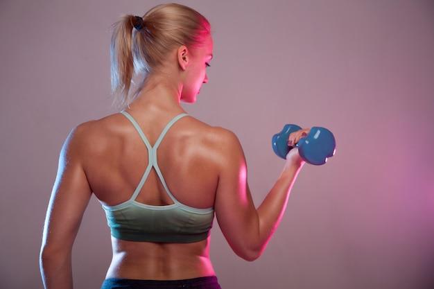 Een blond sportief meisje houdt een halter in haar handen en schudt een gespierde.