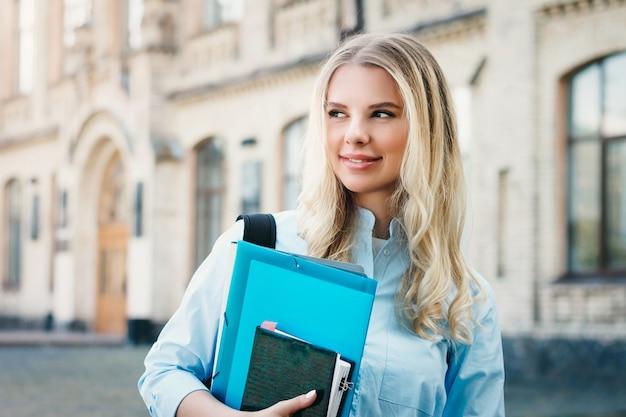 Een blond studentenmeisje glimlacht en houdt een omslag en een notitieboekje in haar handen op een universitaire achtergrond