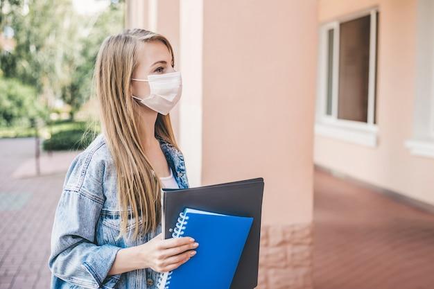 Een blond studentenmeisje met een medisch masker kijkt naar het universiteitsgebouw en komt de deur binnen tijdens de coronavirus-quarantaine