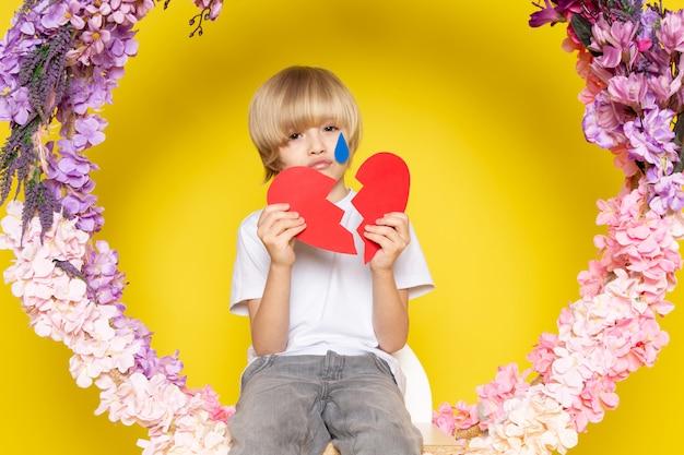 Een blonde blonde jongen in vooraanzicht in witte t-shirt met hartvorm zittend op de bloem maakte staan op de gele vloer