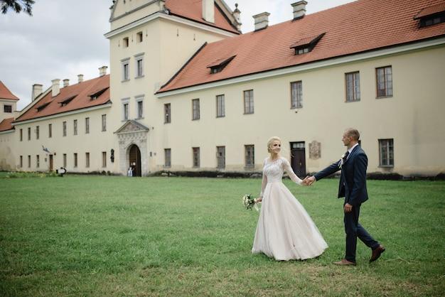 Een blonde bruid leidt haar bruidegom bij de hand