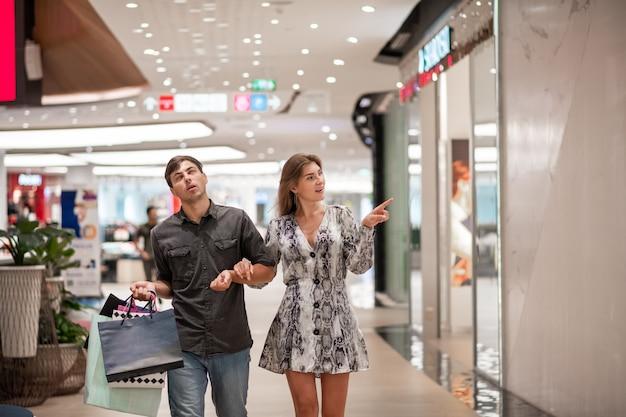 Een blonde in een grijze korte jurk en schoenen, met een man in een grijs shirt en een blauwe spijkerbroek met gekleurde tassen uit de winkel, hand in hand poseren. de man rolt met zijn ogen. het meisje wijst naar een etalage.