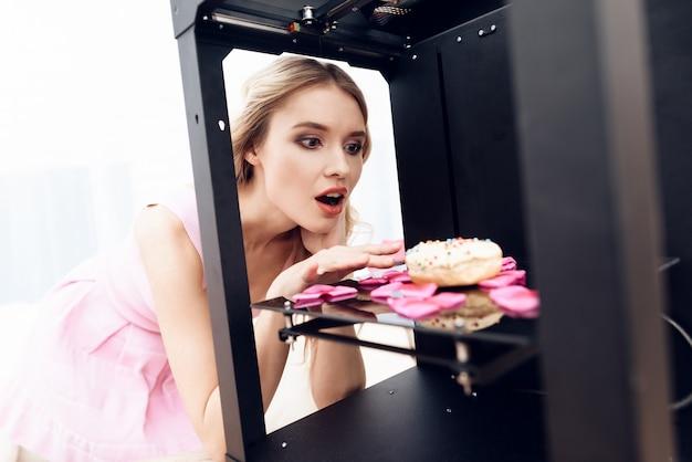 Een blonde in een roze jurk haalt een donut uit een 3d-printer