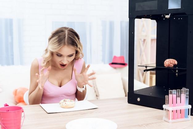 Een blonde in een roze jurk kijkt verbaasd naar een donut.