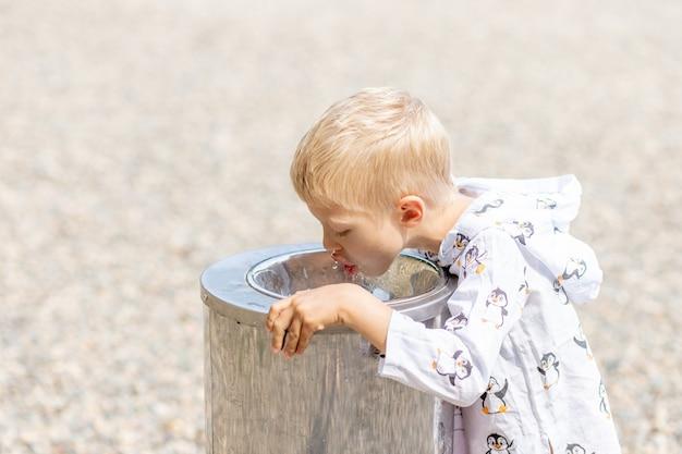 Een blonde jongen drinkt in de zomer water uit een waterdispenser