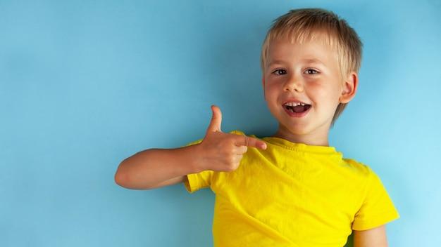 Een blonde jongen in een geel t-shirt glimlacht en steekt zijn duim op