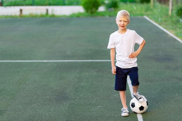 Een blonde jongen in een sportuniform staat op een voetbalveld met een voetbal