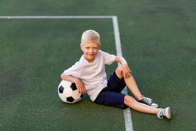 Een blonde jongen in een sportuniform zit met een voetbal op een voetbalveld