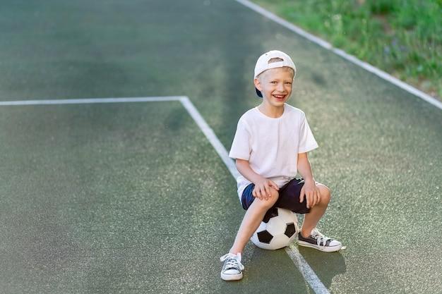 Een blonde jongen met een pet in een sportuniform zit op een voetbal op het voetbalveld