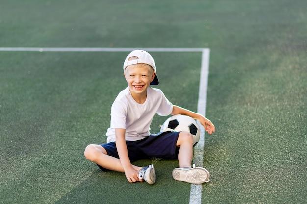 Een blonde jongen met een pet in een sportuniform zit op een voetbalveld met een voetbal