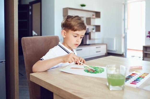 Een blonde jongen tekent op papier met gekleurde verf in de kamer