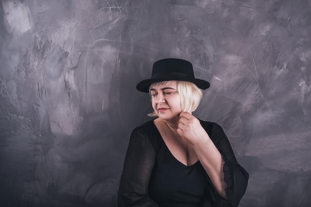 Een blonde, kortharige, mollige oudere vrouw in zwarte kleding en een zwarte hoed op een stevige achtergrond van donkergrijs beton.
