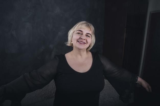 Een blonde, kortharige, mollige oudere vrouw in zwarte kleren op een stevige achtergrond van donkergrijs beton.
