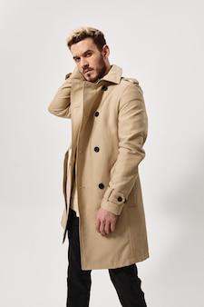 Een blonde man in een beige jas en donkere broek