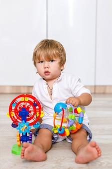Een blonde peuterjongen van europees uiterlijk zit op de vloer van het huis en speelt met felgekleurd speelgoed