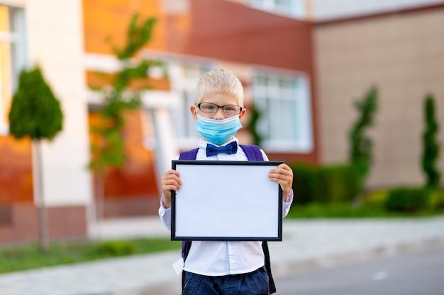 Een blonde schooljongen met bril en een beschermend masker staat op de school en houdt een bord vast met een wit laken. dag van de kennis.