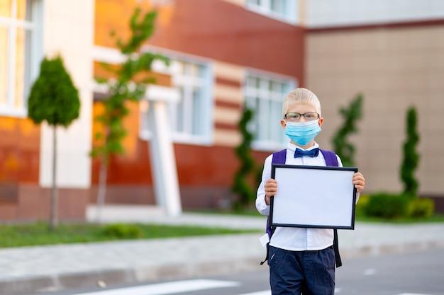 Een blonde schooljongen met bril en een beschermend masker staat op de school en houdt een bord vast met een wit laken.