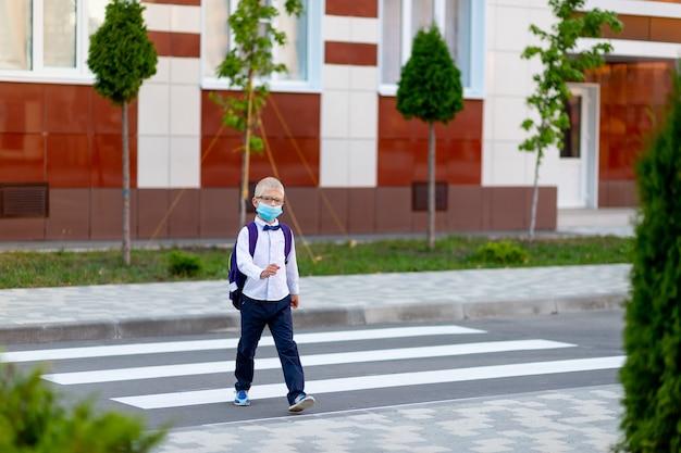 Een blonde schooljongen met bril en rugzak gaat op een voetgangerszebrapad naar school