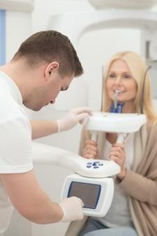 Een blonde vrouw die procedures ondergaat bij de tandarts