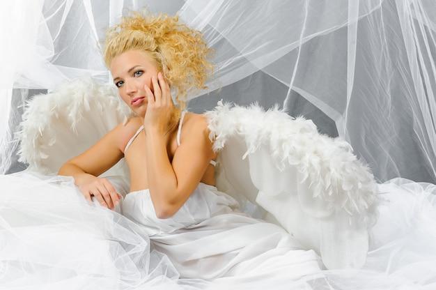 Een blonde vrouw in een engel kostuum poseert voor de camera.