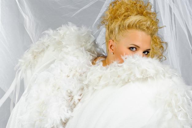 Een blonde vrouw in een engelenkostuum kijkt in een frame door de vleugel.