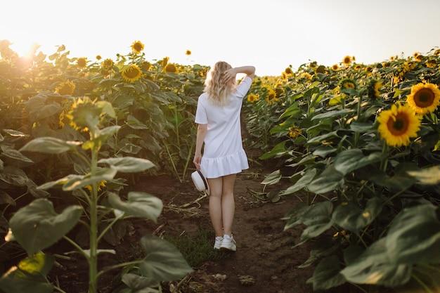 Een blonde vrouw in een witte jurk op het veld met zonnebloemen